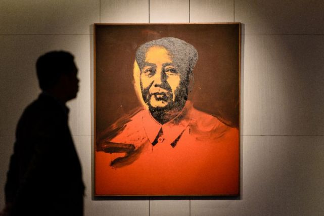 A man walks past 'Mao' a 1973 screen print by US artist Andy Warhol, during a pre-auction preview by Sotheby's in Hong Kong, on March 17, 2017 (AFP Photo/Anthony WALLACE)