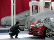 A man takes a photo of the logo on a Tesla Model S sedan at an event in Beijing, China, Tuesday, April 22, 2014. Tesla Motors delivered its first eight electric sedans to customers in China on Tuesday and CEO Elon Musk said the company will build a nationwide network of charging stations and service centers as fast as it can.Ng Han Guan/AP
