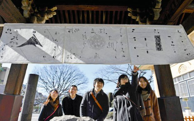 "Visitors look at a set of noren curtains featuring a poem — one of the artworks on display for ""MOT Satellite 2017 Spring by the deep rivers"" — at Joshinji temple in the Kiyosumi-Shirakawa district of Koto Ward, Tokyo."