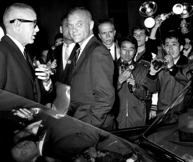 Hideyuki Mihashi ©Stars and Stripes Tokyo, May, 1963: Astronaut John Glenn is mobbed by photographers after his arrival at Tokyo International Airport. Glenn, who in February, 1962 became the first American in orbit, was in Japan to assist with the communications network for the Mercury flight of L. Gordon Cooper. Once the mission was over, he embarked on a 12-day vacation in Japan with his family. John Glenn, a Marine Corps fighter pilot in the Korean War who later served as a U.S. senator and flew a space shuttle mission at age 77, died December 8, 2016.