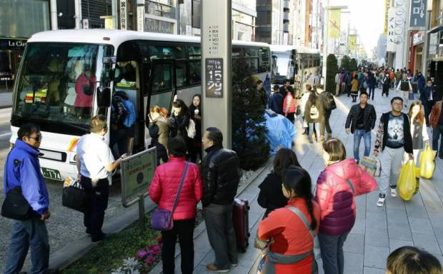 Foreign tourists board a bus after visiting a duty-free shop in Tokyo's Ginza shopping district in January 2016. | KYODO