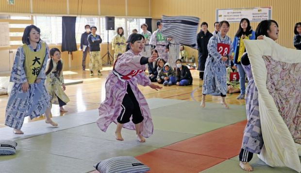 A player throws a pillow at opponents while a libero, right, defends their teammates using a futon as a shield in the fifth all-Japan pillow fight championship at Ito Onsen hot spring resort.