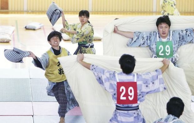 The Yomiuri Shimbun A captain, left, hurls a pillow toward an opponent.