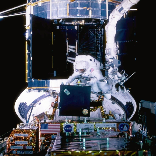 Image above: Astronaut Steve Smith carefully removes STIS from the protective enclosure that carried it into orbit aboard the Space Shuttle Discovery. Image Credits: NASA/ESA.