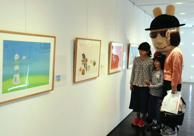 "Visitors, with the character Yanase Usagi behind them, view illustrations on display at an exhibition introducing the magazine ""Ichigo Ehon"" at the Poem and Marchen Gallery in Kami, Kochi Prefecture, on March 18."