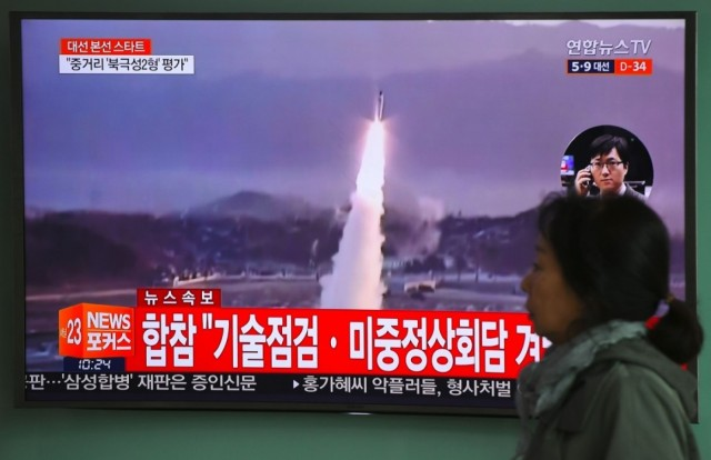 A woman walks past a television screen showing file footage of a North Korean missile launch, at a railway station in Seoul. (AFP/Getty Images)