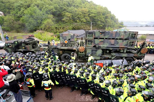 U.S. military vehicle moves as South Korean police officers try to block residents and protesters who oppose a plan to deploy an advanced U.S. missile defense system called Terminal High-Altitude Area Defense, or THAAD, in Seongju, South Korea, on Wednesday. Associated Press.