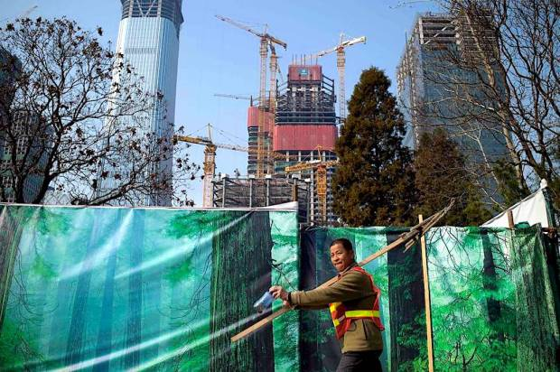 A construction worker walks by a building site in Beijing. Photo: Agence France-Presse/Getty Images