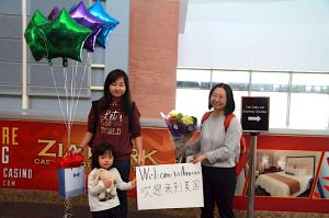 """In this March 17, 2017, photo released by China Aid, Chen Guiqiu holds a """"Welcome to America"""" sign with her daughters Xie Yajuan, 15, and Xie Yuchen, 4, at an airport in Texas."""