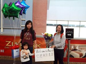 "In this March 17, 2017, photo released by China Aid, Chen Guiqiu holds a ""Welcome to America"" sign with her daughters Xie Yajuan, 15, and Xie Yuchen, 4, at an airport in Texas."