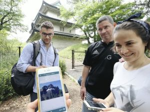 The Yomiuri Shimbun Tourists use the new guide app downloaded on a smartphone in the Imperial Palace in Chiyoda Ward, Tokyo, on Tuesday.