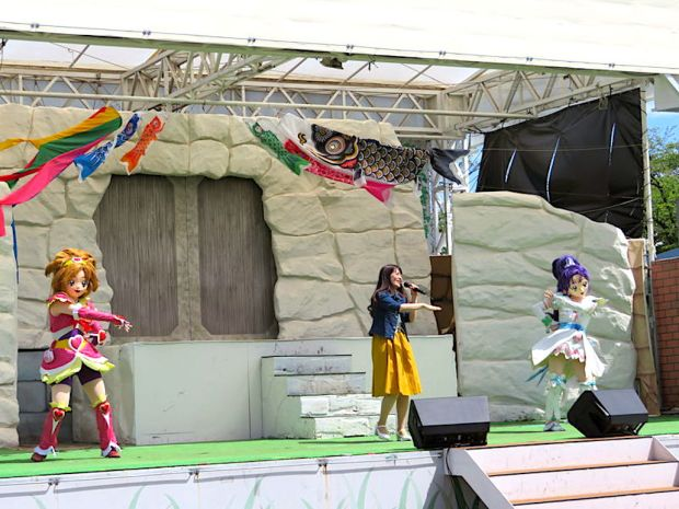 "Yuka Uchiyae, center, sings with ""Futari wa PreCure Splash Star"" lead characters on her sides at the Yomiuriland amusement park in Tokyo."