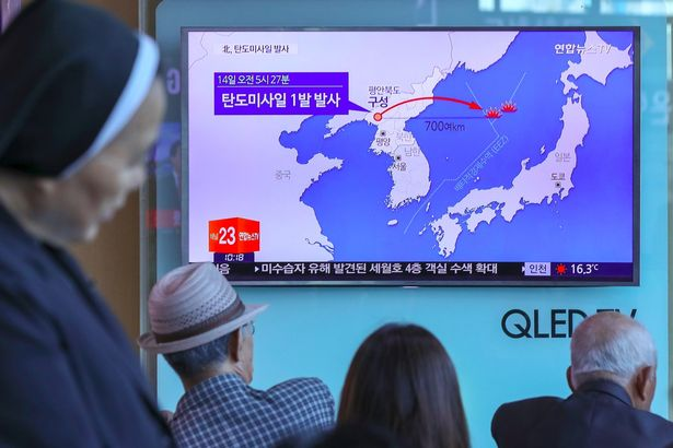 People watch a television news programme, showing file footage of a North Korean missile launch, at a railway station in Seoul (Photo: AFP)