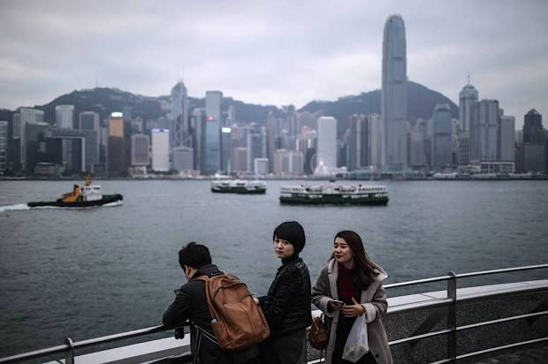 Tourists from mainland China paused on a viewing deck across from Hong Kong's Central district in December. PHOTO: DALE DE LA REY/AFP/GETTY IMAGES