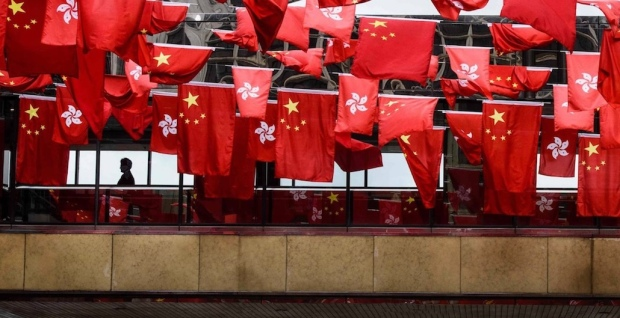 A man walked on a passageway connecting two buildings behind a display of Chinese and local flags in Hong Kong on June 27. On July 1, Hong Kong will observe the 20-year anniversary of its return to Chinese sovereignty. ANTHONY WALLACE/AGENCE FRANCE-PRESSE/GETTY IMAGES
