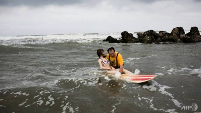 Senji Nakajima takes his rubber girlfriend Saori surfing and skiing. (Photo: AFP)