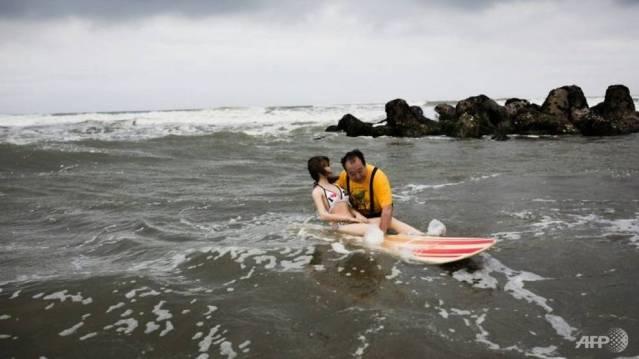 Senji Nakajima takes his rubber girlfriend Saori surfing and skiing. (Photo: AFP)