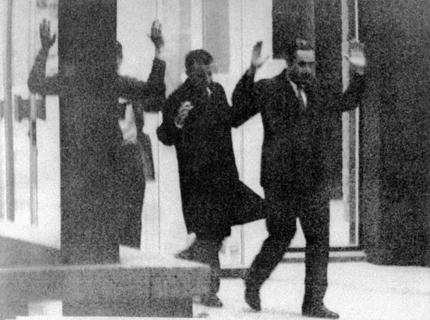 People who had been taken hostage in the Japanese Red Army's attack on the French Embassy in The Hague walk out of the embassy with their hands up after they were freed in September 1974. | AP / VIA KYODO