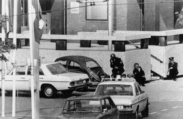 Police crouch against a wall at the French Embassy in The Hague where hostages were held by Japanese Red Army guerillas in September 1974. | KYODO