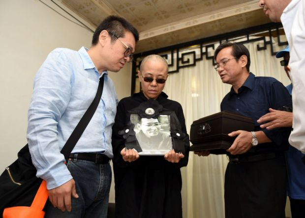 Shenyang Municipal Information Office / via Reuters Liu Xia, wife of deceased Chinese Nobel Peace Prize-winning dissident Liu Xiaobo, holds his picture during his funeral in Shenyang, China, in this photo released by Shenyang Municipal Information Office on Saturday.