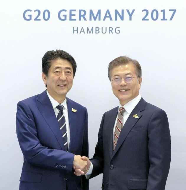 The Yomiuri Shimbun Prime Minister Shinzo Abe shakes hands with South Korean President Moon Jae In in Hamburg on Friday.