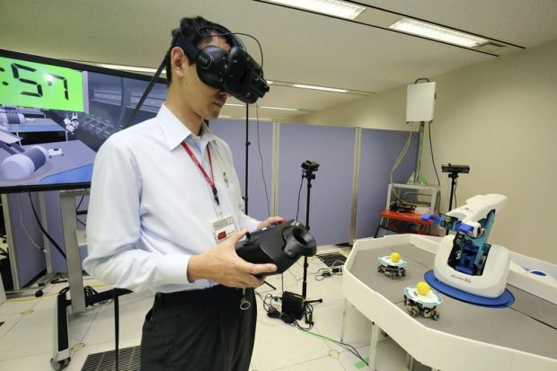 A person wearing a VR headset operates a robot arm as part of NTT Docomo's 5G experiment in Yokosuka, Kanagawa Prefecture. The Yomiuri Shimbun