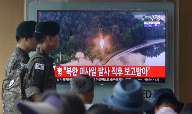 Army soldiers walk by a TV news program showing a file image of a missile being test-launched by North Korea in Seoul on Tuesday.