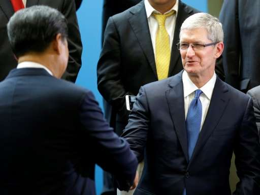Chinese President Xi Jinping, left, shakes hands with Apple CEO Tim Cook, right, during a gathering of CEOs and other executives at Microsoft's main campus in 2015
