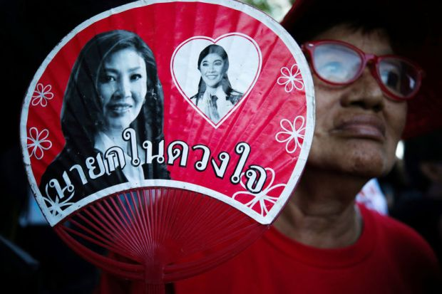A supporter holds a picture of ousted former Thai Prime Minister Yingluck while waiting for the verdict in a negligence trial in Bangkok