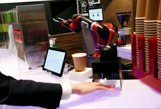 A man scans a QR code printed on a ticket used to order a coffee from the robot barista called